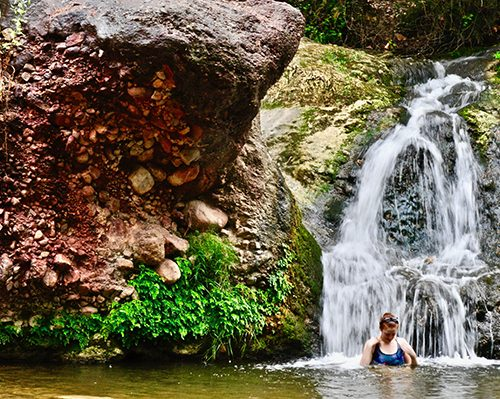 marianna cooling off under a waterfall after hiking in cingles de berti